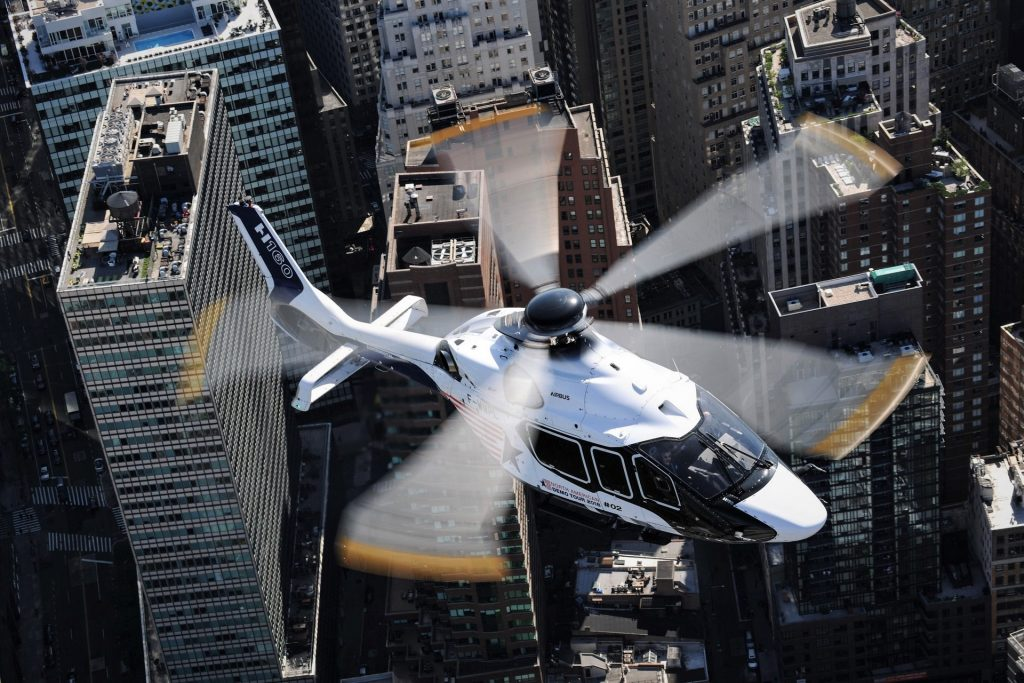 airbus ach160 coprorate helicopter flying over a city